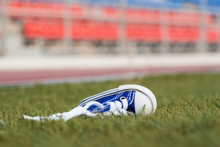 defeated: 1 sneakers lying on a football field. Concept of losing, tired, defeated, fall, pain