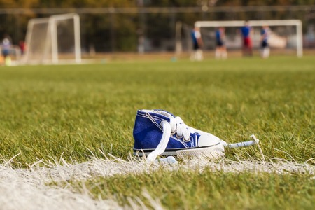 defeated: Standing sports shoe on a background of a football field with the players. Selective focus. Sport concept, despair, defeated