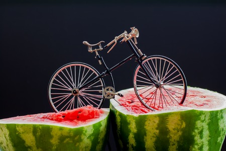 ludicrous: Sur. Vintage bicycle standing on top of a large cut in half scarlet ripe watermelon Stock Photo