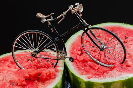 paradox: Paradox. Vintage bicycle standing on top of a large cut in half scarlet ripe watermelon