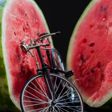 Small model of a retro vintage bicycle near a big cut in half scarlet ripe watermelon