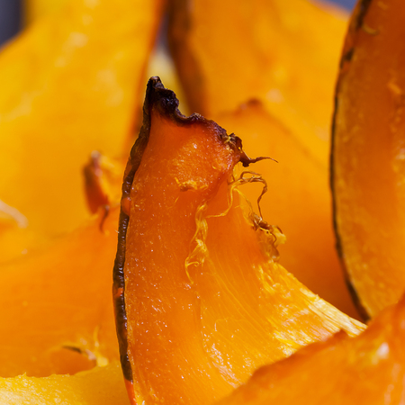 autumn colour: Sliced of baked vivid colour pumpkin on the baking sheet close up, hot dessert in autumn