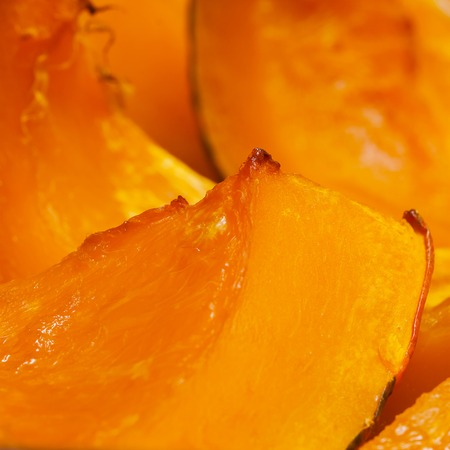 autumn colour: Vivid orange colour slices of baked pumpkin with a honey, hot dessert in autumn, square