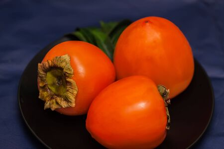 Sweet and pulpy of ripe golden three persimmons can be eaten fresh, dried, raw, or cooked Stock Photo