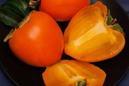 Cut a ripe persimmon in black plate, low key. Sweet, delicious flesh of Persimmon is packed with vitamins, minerals, antioxidants vital for optimum health Stock Photo