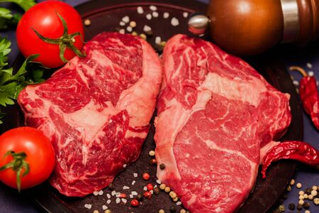 flesh eating animal: Marmara meat has a delicate taste and It contains ingredients that prevent the formation of Bad cholesterol. Raw juicy steaks from marble beef with seasonings on dark wooden background.