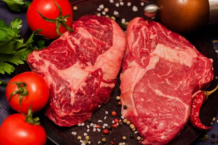 Marble beef for the perfect steak. Raw meat steak on dark wooden background ready to roasting with tomatoes, parsley and spices. Stock Photo