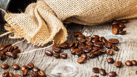 Roasted coffee beans on a brown wooden background with coarse roughly woven burlap, grunge texture. Place for your text