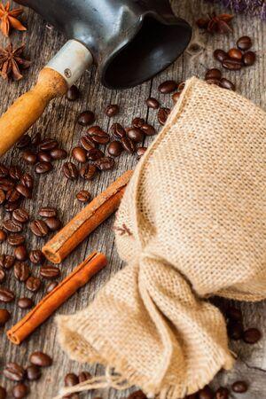 burlap sac: Roasted coffee beans with burlap sac, Cezve, on old weathered wood, cinnamon, anis. Vintage, rustic background . Top view.