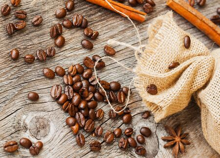 Roasted coffee beans with burlap fabric old weathered wood and spices. vintage background use. Top view. Place for text Stock Photo