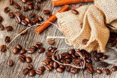 Roasted coffee beans , coarse burlap sac and cinnamon on old wooden table. Top view, grunge texture. With place for your text