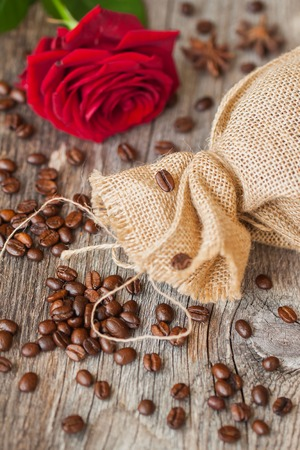 Roasted coffee beans on a brown wooden background with coarse roughly woven burlap and red rose, grunge texture. Top view. Place for your text