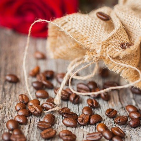Roasted coffee beans on a brown wooden background with coarse roughly woven burlap and red rose, grunge texture. Place for text Stock Photo