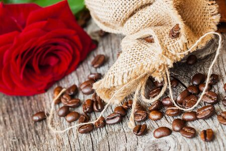 burlap sac: Roasted coffee beans, fresh red rose, coarse burlap sac on old wooden table. Vintage still life. Place for text. Top view.