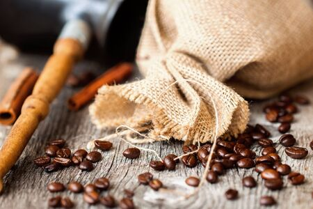 burlap sac: Roasted coffee beans, burlap sac, Cezve, rustic wooden table, cinnamon. Vintage background . Place for text. Top view.