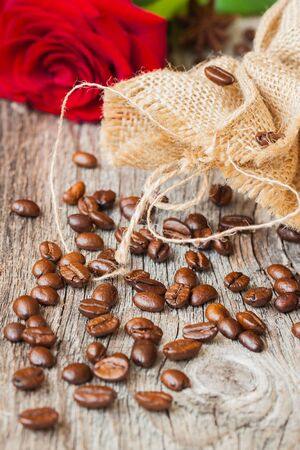 Roasted coffee beans, fresh red rose, coarse burlap sac on old wooden table. Vintage still life. Place for text. Top view.