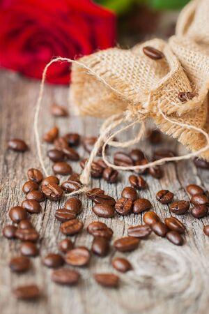 Geröstete Kaffeebohnen auf einem braunen hölzernen Hintergrund, grob grob gewebte Sackleinen und rote Rose, Grunge Texturen. selektiver Fokus. Konzept romantischer Morgen mit Ihrem Liebling Standard-Bild