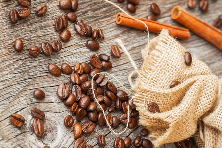 Roasted coffee beans, burlap sac, rustic wooden table, cinnamon. Vintage background, grunge texture. Top view.