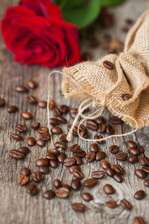burlap sac: Roasted coffee beans, fresh red rose, coarse burlap sac on old wooden table. Vintage still life. Place for text. Top view. Concept romantic morning with your favorite. Top view Stock Photo