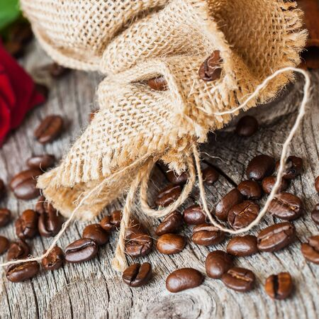 burlap sac: Roasted coffee beans, burlap sac, rustic wooden table, cinnamon. Vintage background . Place for . Top view.
