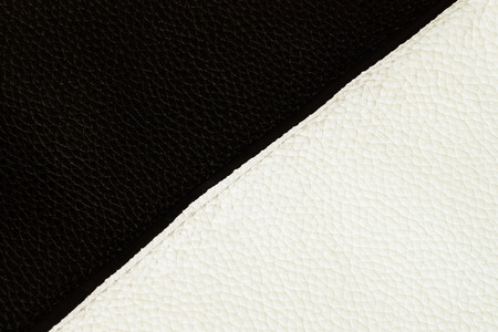 Texture of black and white genuine leather close-up sewn with stitch. For background , backdrop, substrate, composition use. Always fashionable classic color combination.