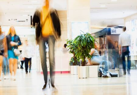 adolescencia: Abstract defocused motion blurred young people walking in the shopping center. Figure of one person close-up, urban lifestyle concept, background.