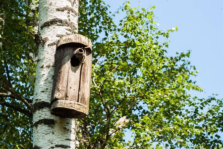 Simple old birdhouse in a rustic style. Concept of the season, guest house, own housing, natural materials. Modern background