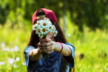 Girl with long hair in a cap holds out bouquet of chamomile, daisies to us, in front of face. Natural soft blurred background