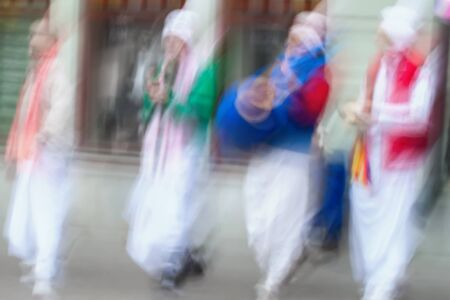 vedas: Young people group of Hare Krishna, Believers of Society for Krishna Consciousness in streets of city plays drums, other instruments, sing Hindu mantra. Abstract blur