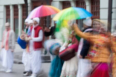 vedas: People group of Hare Krishna movement singing, dancing in the streets of city with words Hare Krishna. Bright clothes, umbrellas, musical instruments. Defocused blur