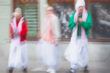 vedas: Abstract defocused motion blurred Young people group of Hare Krishna movement singing and dancing in the streets of the city with the words Hare Krishna. Stock Photo