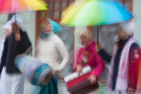 vedas: People group of Hare Krishna, Believers of Society for Krishna Consciousness in the streets of city plays instruments, sing mantra. Abstract defocused motion blurred