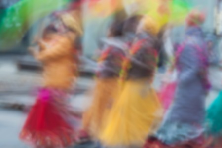 vedas: Girls in bright clothes, group of Hare Krishna movement singing and dancing in the streets of the city with the words Hare Krishna. Abstract defocused motion blurred