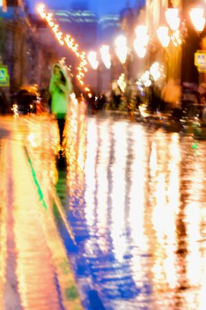 intentional: Abstract background of Girl in bright green coat. Bright reflections of street lamps in wet asphalt Intentional motion blur. Concept of modern city.