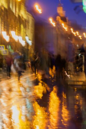 intentional: Abstract background of blurred people figures under umbrellas, city street in rainy evening, orange-brown tones Intentional motion blur. Concept of seasons, weather, modern city.
