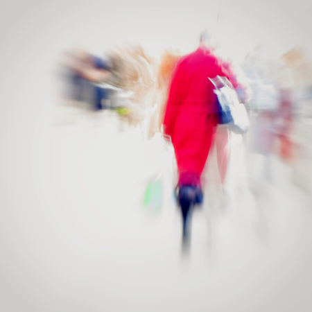 intentional: Abstract background. Intentional motion blur. Girl with handbag in red coat walking on the sidewalk. Concept of seasons, shopping, walking, lifestyle, modern city.
