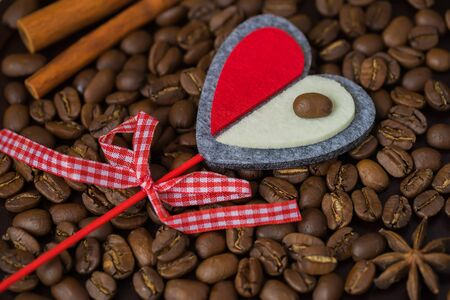 Grains of coffee close-up and decorative red heart. Concept of love with coffee or a loved one. Image for any day, especially for a happy Valentines day