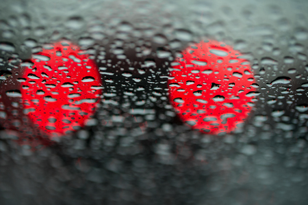 imminence: Abstract background for the banner. Two night lights of city transport were seen through the windshield in rainy weather. Concept of threat, danger, hazard, peril
