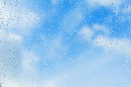 Textured blue background of sky, natural water drops on window glass, rain texture. Concept of clear, pure, bright, renovated. Modern background with text, wallpaper Stock Photo