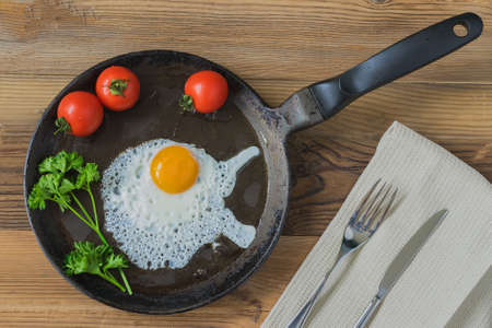 good cholesterol: Healthy homemade breakfast with fried fresh eggs on pan served with tomatos, cutlery on a tissue napkin. Top rustic view