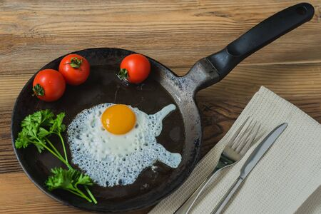 good cholesterol: Fried egg with parsley greens, tomatoes on the pan with napkin, fork and knife. Delicious healthy breakfast