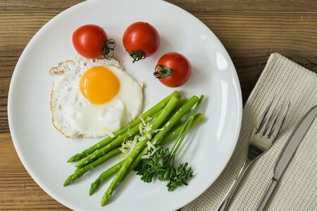 Healthy homemade breakfast with fried eggs and fresh asparagus on plate close-up, served with tomatos. Top view Stock Photo