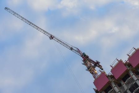 Specially diagonal image of construction tower crane next to building under construction against the background of the blue sky. Unusual foreshortening. Copy space