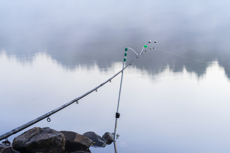 Fishing rod on the bank, quiet early morning on lake, dawn, first rays of the sun. Seasons, environment, natural beauty, summer hobbies, leisure, lifestyle on vacation