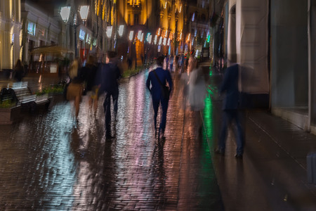 intentional: Abstract background of blurred young people walking down street in rainy evening, Impressionism style, colorful lighting. Intentional motion blur. Seasons, weather, modern city, lifestyle, leisure.