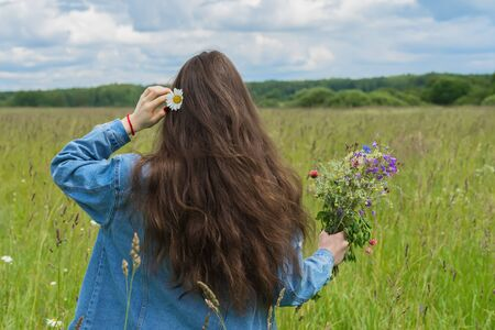 daisie: Unrecognizable young girl with daisie in her hair and beautiful summer bouquet of wild flowers in hand standing on background of green field. Seasons, environment, summer hobbies, recreation, lifestyle