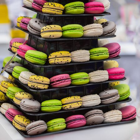Pyramid of different french colorful macaroons various flavors and diffrent colors, french sweet cookies from almond flour, on market counter
