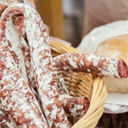 Close-up of traditional italian tasty delicacies in wicker basket, picant organic salami in the market. Gastronomic products for gourmets Stock Photo