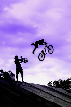 BMX bike jumping in sky on high speed, black silhouette against bright sky. Extrem Sport and risk. Stock Photo