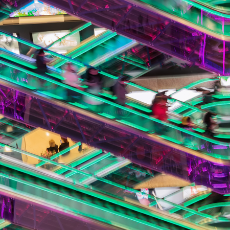 Abstract blurredn image of shopping mall, unrecognizable silhouettes of people on escalators with bright led backlight, modern background for design. Motion effect Stockfoto